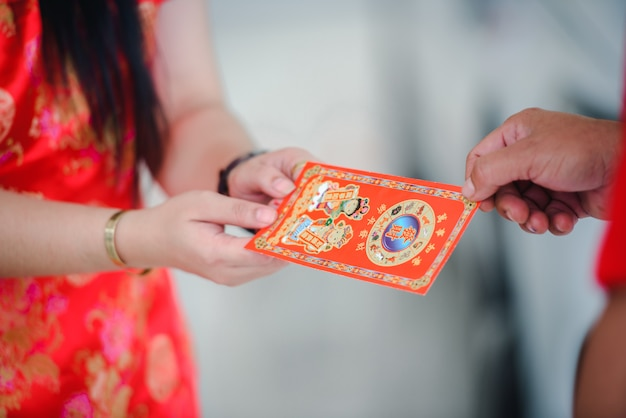 The supervisor give ang pao a gift for chinese new year with a beautiful asian woman.