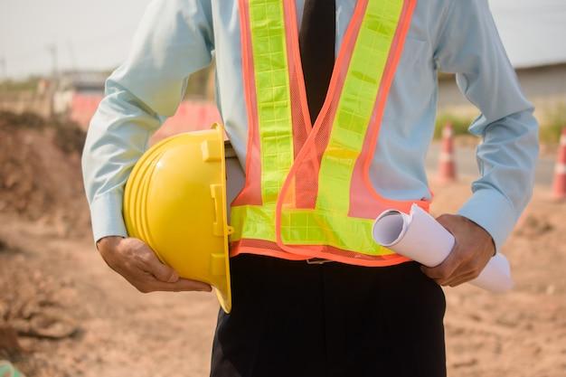 建設現場でヘルメットを保持している監督