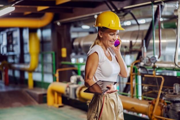 Супервайзер держит планшет и разговаривает по телефону, стоя на теплоцентрали.