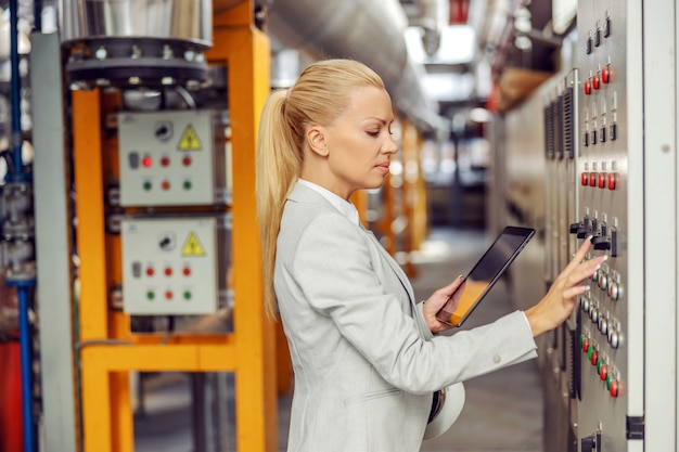 ダッシュボードの隣の暖房設備に立ち、設定を調整し、タブレットを持っているスーパーバイザー。