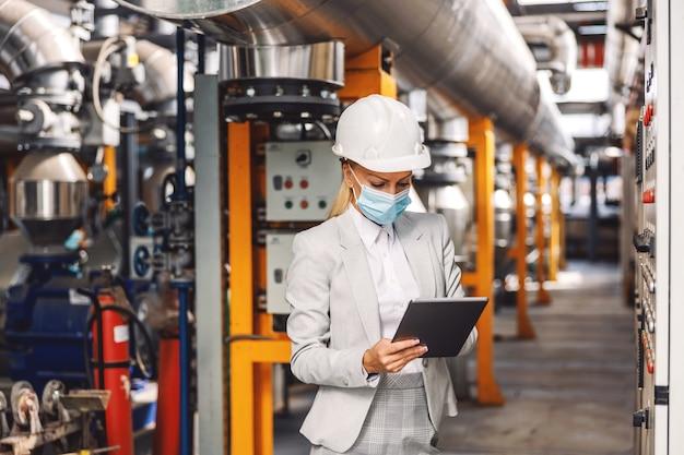 Супервайзер стоит на теплоцентрали рядом с приборной панелью и держит планшет во время пандемии короны.