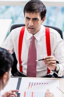 Supervisor talks to subordinate professional in office building