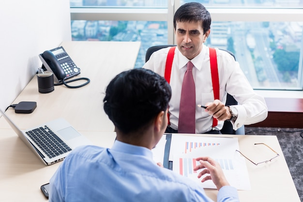 Supervisor talks to subordinate professional in office building