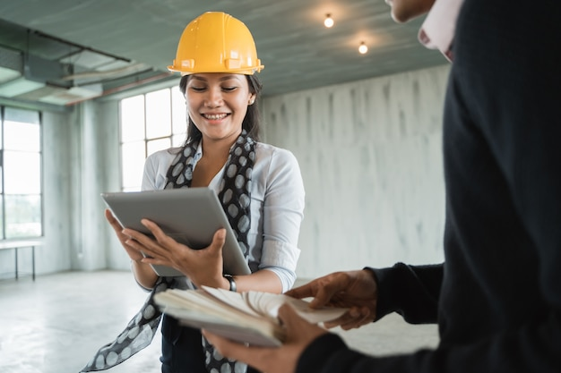 Supervisor woman engineer looking a property design on tablet digital