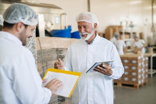 Инспекторы говорят о качестве еды. в руках диаграмма и планшет.