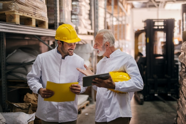 Supervisors using tablet in warehouse.