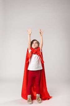 빨간 망토를 입은 슈퍼우먼 아이가 손을 들었다