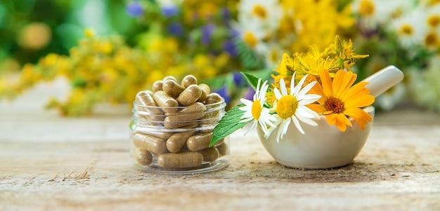 Добавки и травы в миске и стеклянных банках на деревянном столе с размытым фоном цветов