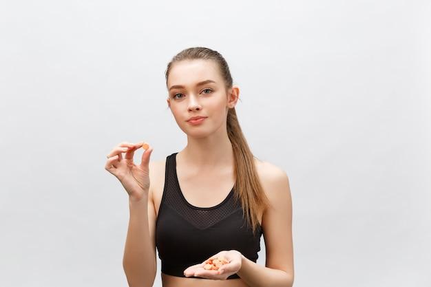 Пищевые добавки, спорт, витамины, диета, питание, здоровое питание, образ жизни. закройте улыбающейся женщины фитнеса, принимающей таблетку с рыбьим жиром омега-3, витамином d, e, a рыбьим жиром.