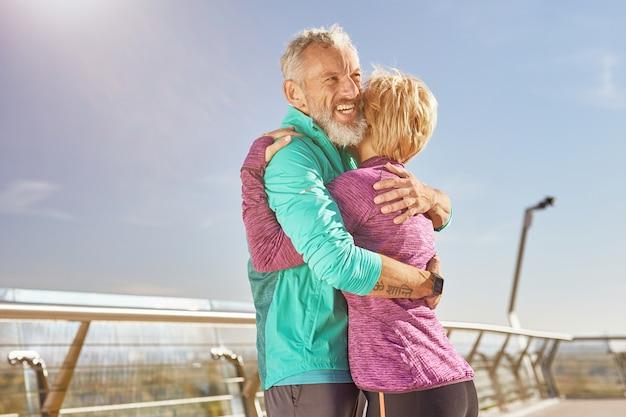 운동복 차림으로 행복한 성숙한 가족 커플을 지원하고 체육관에서 운동한 후 포옹하면서 웃고 있습니다.