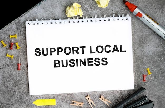 Поддержите местный бизнес текст на белом блокноте с булавками, маркером и степлером на бетонном столе.