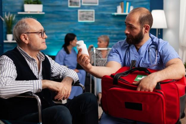 지원 간호사 직원은 치료 중 손에 응급 의약품 키트 가방을 들고 있는 노인에게 약 치료를 설명합니다. 사회 서비스 간호 노인 은퇴한 남성. 의료 지원
