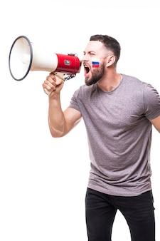 Поддержи россию. крик в мегафон российский футбольный болельщик в игре в поддержку сборной россии на белом фоне. концепция футбольных фанатов.