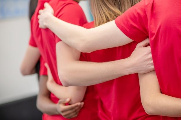 지원, 연합. 빨간 티셔츠로 자원 봉사자의 등을 껴안는 친절한 손, 얼굴이 보이지 않음