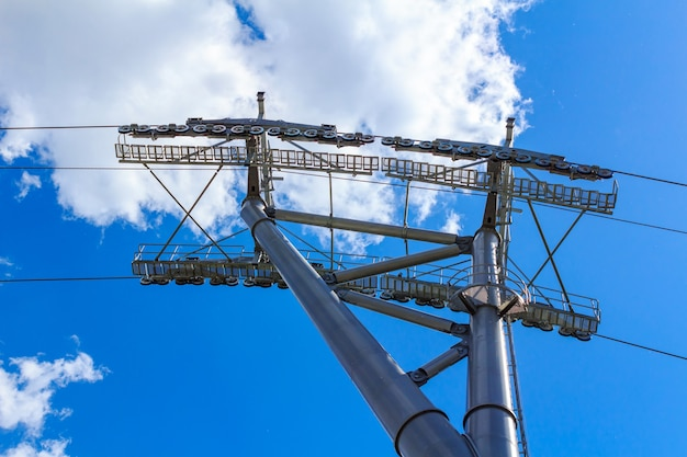 Support with ropes and rollers of ropeway close-up against blue sky with white clouds