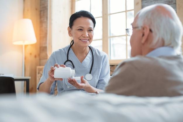 Поддержите свой организм. веселый позитивный доктор, несущий бутылку с таблетками, глядя на старшего мужчину