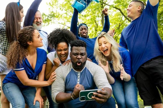 Болельщики наблюдают за победой своей команды на мобильном телефоне