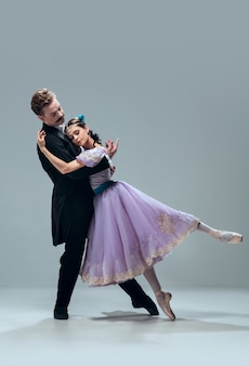 Supporting. beautiful contemporary ballroom dancers isolated on grey studio background. sensual proffessional artists dancing walz, tango, slowfox and quickstep. flexible and weightless.