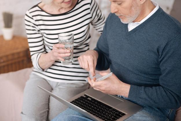 서로를 지원합니다. 그의 아내가 그를 위해 물 잔을 들고있는 동안 케이스에서 약을 복용하려고하는 노인의 상위 뷰.