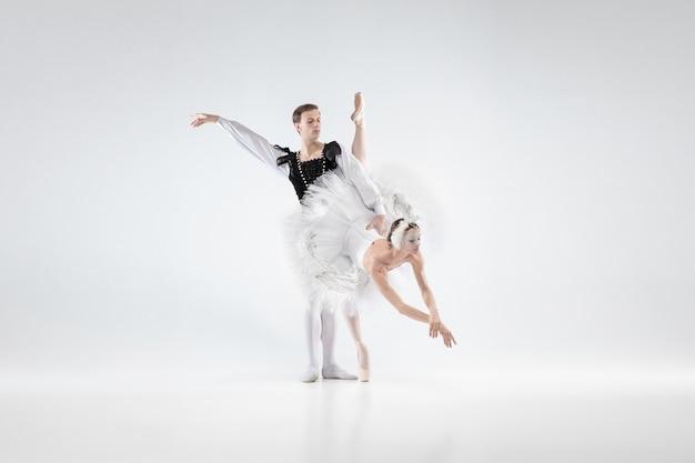 サポート。白いスタジオの背景に分離して踊る優雅なクラシックバレエダンサー。白鳥のキャラクターのような優しい服を着たカップル。優雅さ、芸術家、動き、行動、動きの概念。