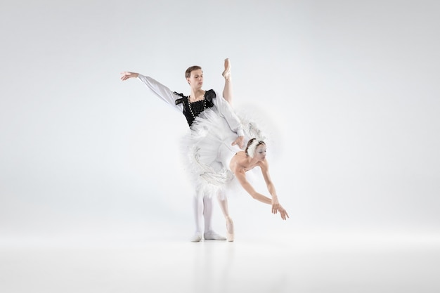 Supporting. graceful classic ballet dancers dancing isolated on white studio background. couple in tender clothes like a white swan characters. the grace, artist, movement, action and motion concept.