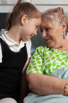 臨床記録中に愛を示す年配の祖母と額に触れる孫娘をサポートしています...