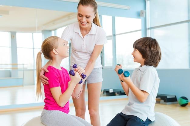 トレーニングで子供たちをサポートします。ヘルスクラブでの運動で子供たちを助ける陽気なインストラクター