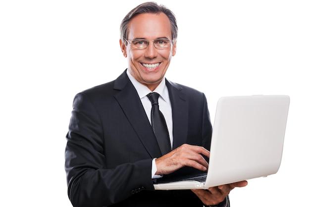 Поддержка вашего бизнеса. уверенный зрелый мужчина в формальной одежде работает на ноутбуке и улыбается, стоя на белом фоне
