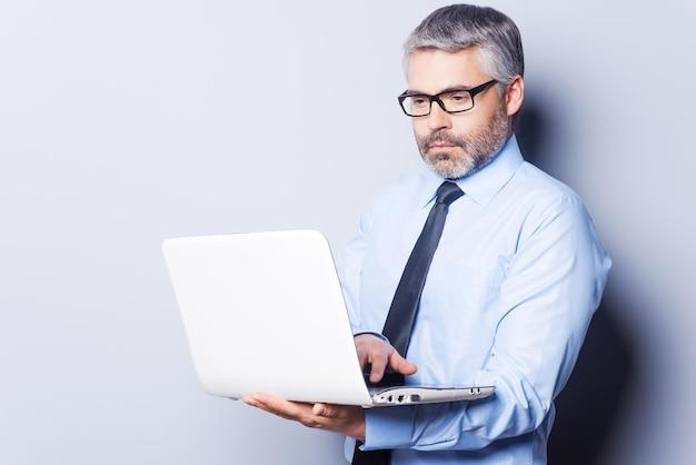 Поддержка вашего бизнеса. уверенный зрелый мужчина в формальной одежде, работающий на ноутбуке, стоя на белом фоне