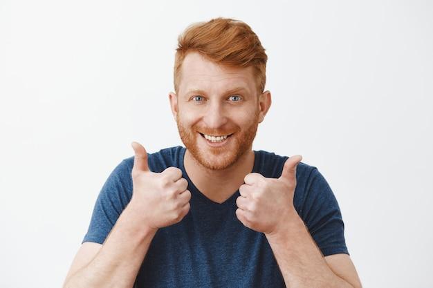 Поддерживающий и привлекательный взрослый рыжий мужчина с щетиной, любящий отличный план, поднимает руки, показывает вверх большие пальцы и радостно улыбается