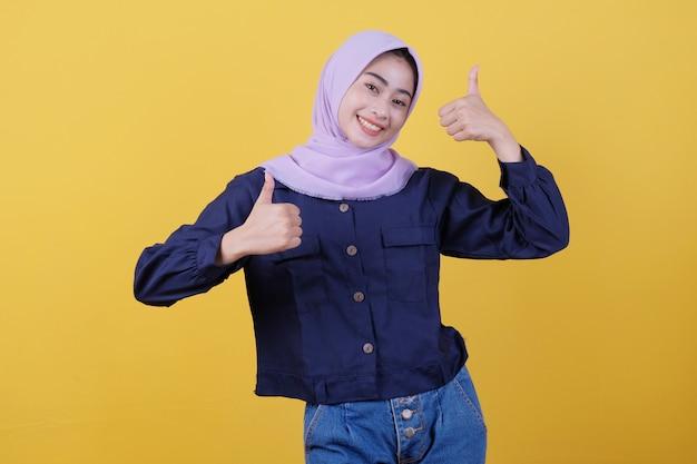ヒジャーブを身に着けている両方のアジアの女性が彼らの親指を感動させて幸せに見せ、肯定的な答えを与える製品が好きで、黄色い壁の上にそれを勧めて、支持的で楽観的な幸せ