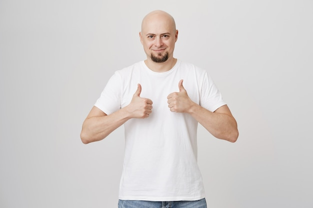 Supportive bald adult man with beard showing thumb-up in approval