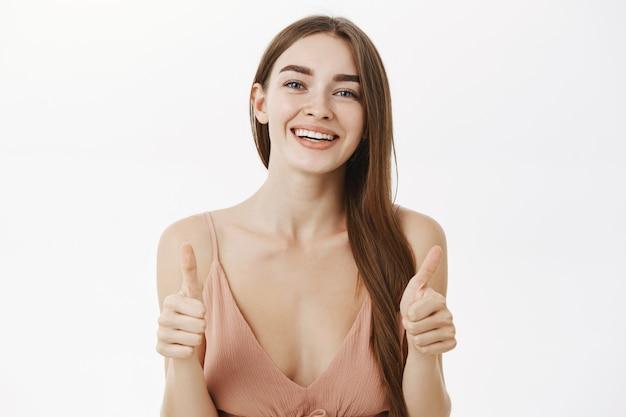 Поддерживающая очаровательная и элегантная женщина с длинными каштановыми волосами в бежевом платье показывает палец вверх