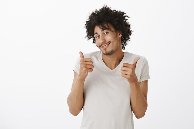 Ragazzo carino solidale che mostra i pollici in su. l'uomo felice e contento approva la scelta, elogia o fa i complimenti a te
