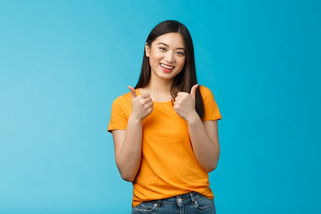 Supportive cute friendly asian girl give thumbs up and smiling, cheering for you, congratulate nice work, approving good idea, like nice outfit, grinning glad accept plan, stand blue background.