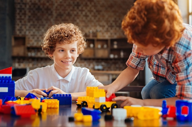 Supportive elations. selective focus on a curly haired boy smiling broadly while sitting at a table and looking at his little brother while both playing with a construction set.