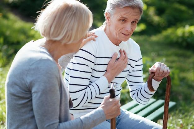 Поддерживающая пожилая больная пара плохо себя чувствует и поддерживает друг друга, держа палки и сидя на скамейке на открытом воздухе