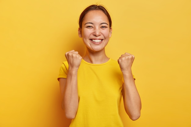 Supportive good looking triumphs with success, raises clenched fists, smiles happily, has eastern appearance, happy finally gaining goal, glad to fullfil dream, dressed casually poses over yellow wall