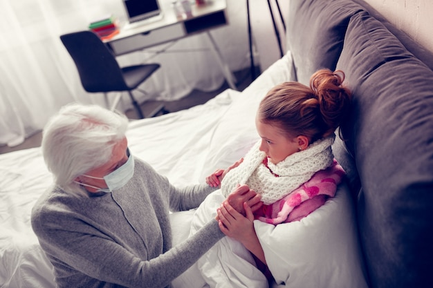 Supportive granny. girl suffering from flue holding hands of her supportive granny wearing protective mask