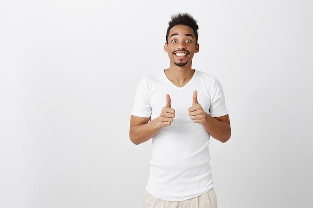 Поддерживающий красивый афро-американский мужчина показывает большие пальцы в одобрении, как идея, хвалит хороший выбор