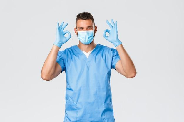 ハンサムな男性看護師、スクラブの医師が大丈夫の兆候を見せ、クリニックでのスクリーニングサービスの質を保証