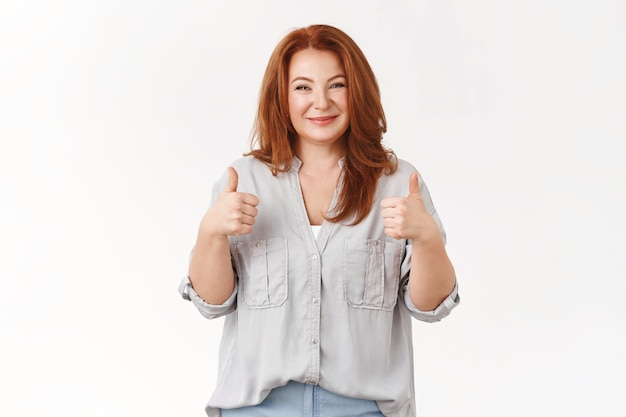 Supportive lovely elegant sincere redhead middle-aged mother proudly smiling happy eyes show thumbs-up cheer encourage daughter feel proud delighted excellent efforts, like result, white wall