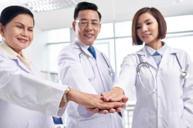Supportive medical coworkers stacking hands to show collaboration is the key to success