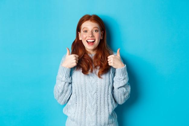 스웨터를 입은 빨간 머리 소녀는 엄지손가락을 치켜들고 놀란 표정을 하고 좋은 선택을 칭찬하며 파란색 배경 위에 서 있습니다.