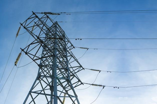 雲のある青空を背景に高圧送電線をサポートします。電気産業。