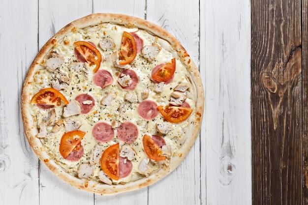 チーズ、トマト、ハム、チキンを使った最高のアソートクラシックピザ。イタリアンピザ