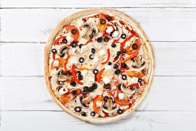 モッツァレラチーズ、マッシュルーム、タマネギ、トマトの最高のクラシックなイタリアンピザ。ピザの理想的な外観
