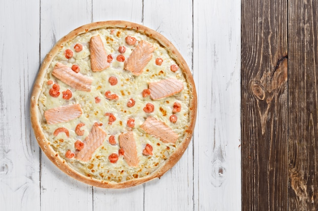 Supreme pizza with salmon and shrimps served on wooden table. seafood pizza