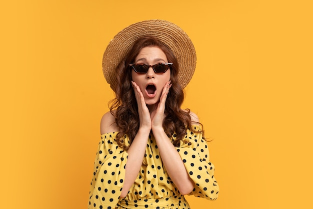 Suprice face. portrait of red head woman in straw hat and stylish sunglasses posing on yellow in summer dress.