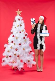 Bella donna sorpresa con il cappello di babbo natale e in piedi vicino all'albero di natale decorato che tiene i regali sul rosso